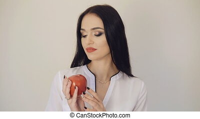 Pretty girl holding and looking on red juicy apple on the background 4K