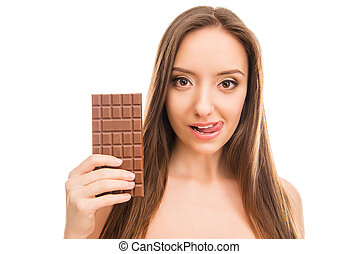 Pretty girl holding bar of chocolate and licking her lips