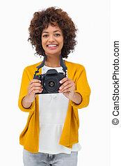 Pretty girl holding digital camera