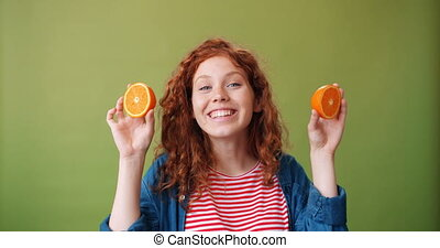 Pretty girl holding fresh oranges near her eyes smiling on green background