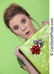 Pretty girl holding gift on green background
