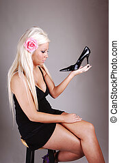 Pretty girl in a black dress holding her shoe.