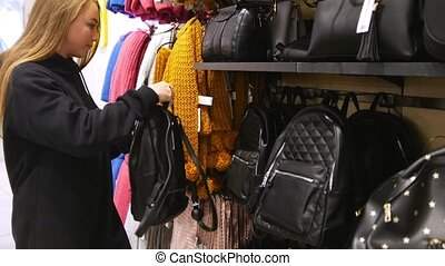 Pretty girl in a mall trying out black bag and backpack