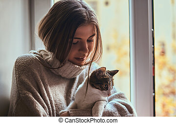 Pretty girl in a warm sweater hugs her favorite cat sitting on the window sill next to the open window