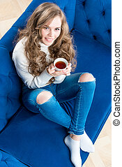 pretty girl in a warm sweater with a cup of tea on the sofa in the living room top view