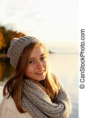 Pretty girl in autumn by the lake