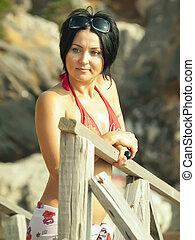 pretty girl in bikini near rocks