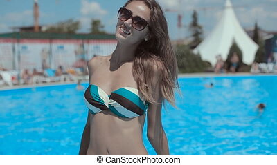 Pretty girl in bikini with long hair near the pool