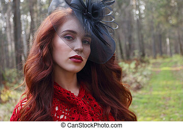 Pretty girl in black hat poses in autumn forest at warm sunny day