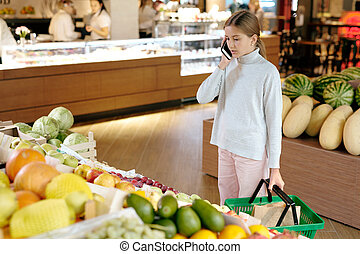 Pretty girl in casualwear talking to her mom on mobile phone by fruit display