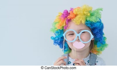 Pretty girl in colored wig is holding glasses and lips - ...