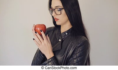 Pretty girl in glasses holding red juicy apple on the background