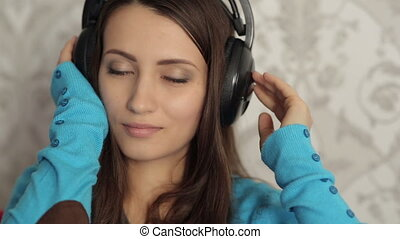 Pretty Girl in Headphones Listening Music on the Sofa