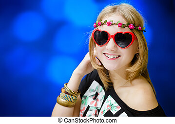 Pretty girl in heart shaped sunglasses on blue bokeh background.