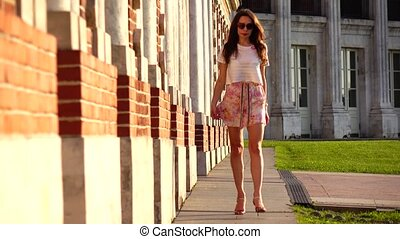 Pretty girl in high heels walking near red brick wall, 4K zoom our video