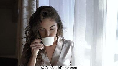 Pretty girl in nighty drinks a cup of coffee near the window