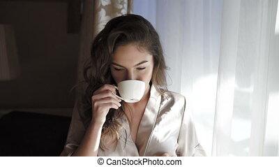 Pretty girl in nighty drinks a cup of coffee near the window in 4K