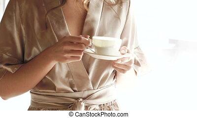 Pretty girl in nighty drinks a cup of coffee near the window. Slowly