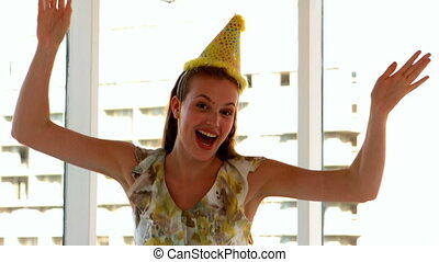 Pretty girl in party hat jumping in slow motion