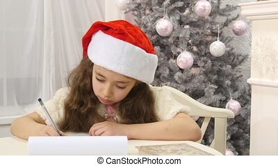Pretty girl in Santa hat writes letter to Santa near christmas tree