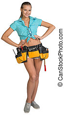 Pretty girl in shorts, shirt and tool belt with tools. Full length