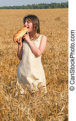 Girl in the field bites a loaf of bread
