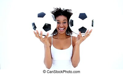 Pretty girl in white holding footballs on white background