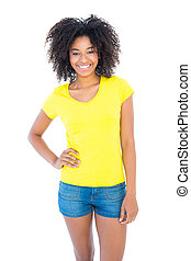 Pretty girl in yellow tshirt and denim hot pants smiling at...