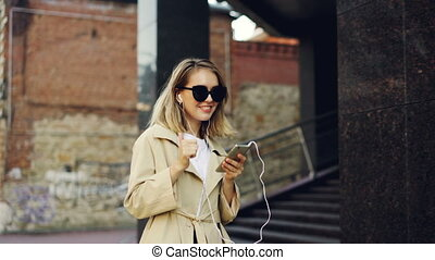Pretty girl is listening to music through earphones using smartphone and dancing walking in the street and enjoying rhythm and modern city. Girl is wearing sunglasses and coat.