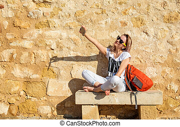 Pretty girl is taking selfie sitting on a bench at the wall