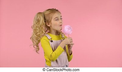 Pretty girl is tasting pink candy on the stick - Pretty...