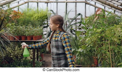 Pretty girl is walking in greenhouse and spraying water on greenery while her busy mother is working in background. Childhood, helping parents and family concept.
