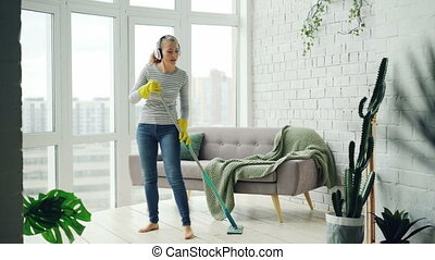 Pretty girl is washing floor with flat plastic mop and...