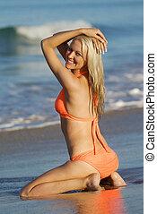 Pretty girl kneeling on sand at beach