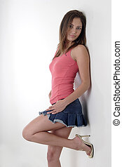 Pretty girl leaning against white wall