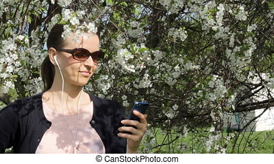 Pretty girl listening to the music in blooming garden