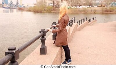 Pretty girl looking at view of port with cranes while standing leaning on embankment of river in city.