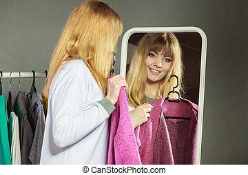 Pretty girl looking into mirror.
