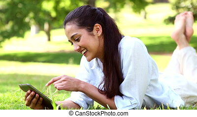 Pretty girl lying on the grass using tablet