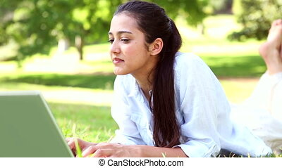 Pretty girl lying on the grass using laptop