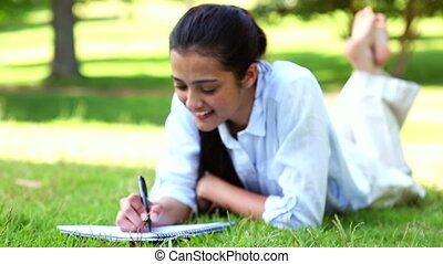 Pretty girl lying on the grass writing on notepad