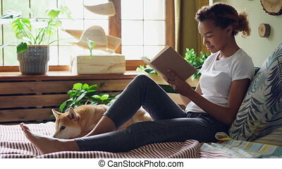 Pretty girl mixed race student is reading book and caressing pet dog expressing love and care sitting on bed in the house. Youth, hobby and animals concept.