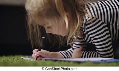 Pretty girl of preschool age with blond hair, dressed in a white and black striped shirt lying on the green carpet in the album draws markers for artists. She likes to feel like an artist