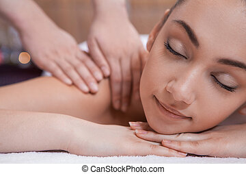 pretty girl on massage table. hand massage of back and candles on background