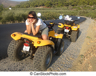 Pretty girl is sitting back to front on yellow quadricycle