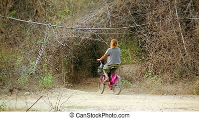pretty girl on the road with her bike traveling laos