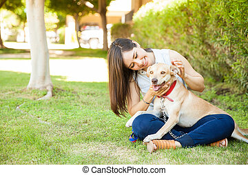 Pretty girl petting her dog outdoors