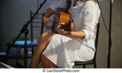 Pretty girl play guitar at stage in the loft or night club