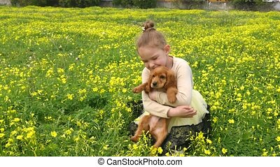 Pretty girl playing on green grass with a puppy