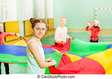 Pretty girl playing parachute games in sports hall